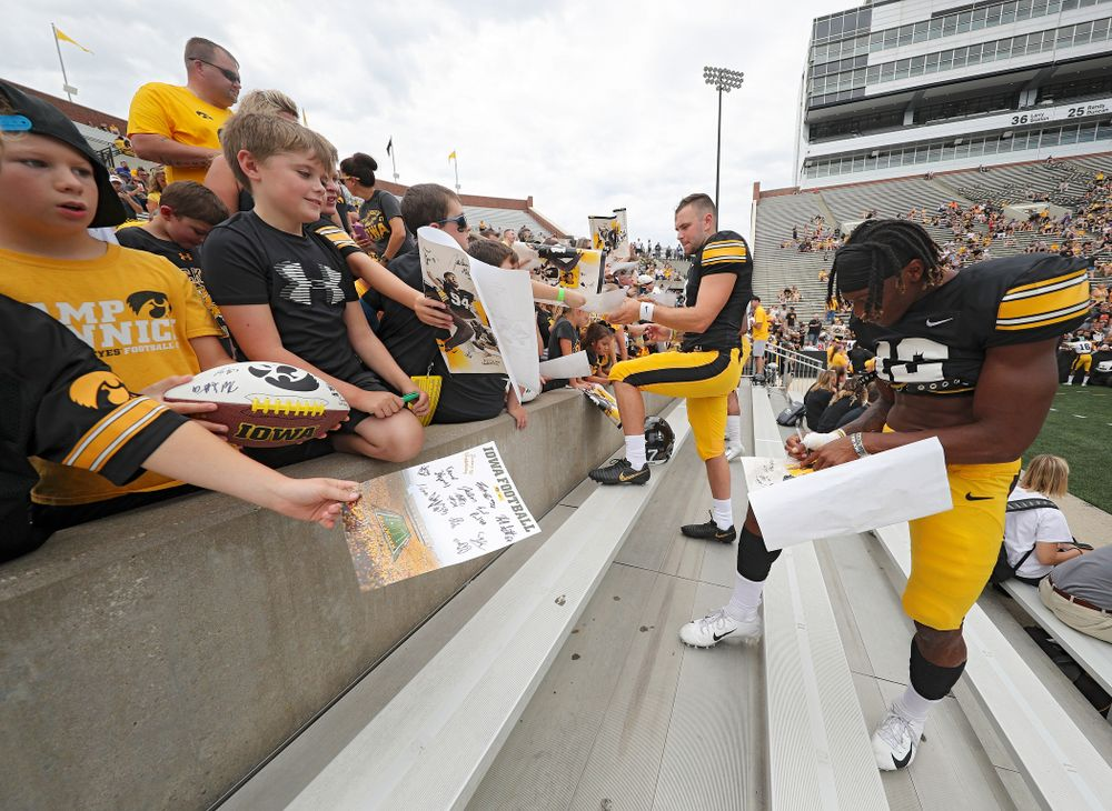 Iowa Hawkeyes wide receiver Brandon Smith (12) signs an autograph during Kids Day at Kinnick Stadium in Iowa City on Saturday, Aug 10, 2019. (Stephen Mally/hawkeyesports.com)