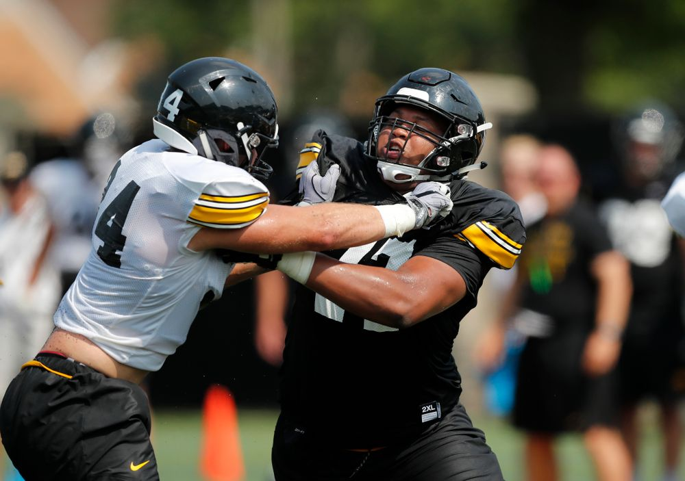 Iowa Hawkeyes offensive lineman Alaric Jackson (77) and linebacker Kristian Welch (34) during fall camp practice No. 9 Friday, August 10, 2018 at the Kenyon Practice Facility. (Brian Ray/hawkeyesports.com)