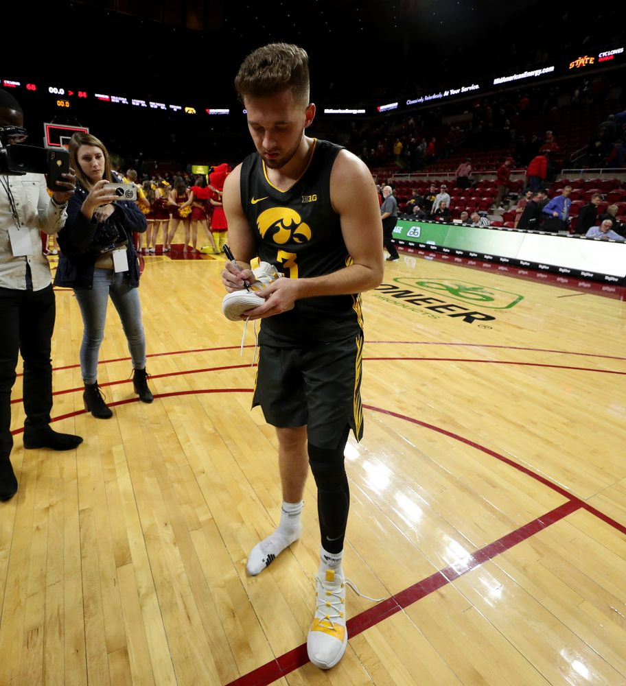 Iowa Hawkeyes guard Jordan Bohannon (3) writes  a message on his shoes before leaving them on the court following their game against the Iowa State Cyclones Thursday, December 12, 2019 at Hilton Coliseum in Ames, Iowa(Brian Ray/hawkeyesports.com)