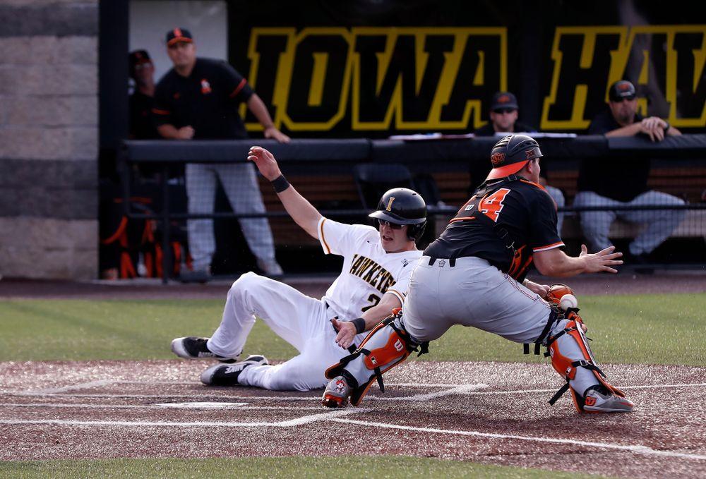 Iowa Hawkeyes catcher Austin Guzzo (20) scores against the Oklahoma State Cowboys Saturday, May 5, 2018 at Duane Banks Field. (Brian Ray/hawkeyesports.com)
