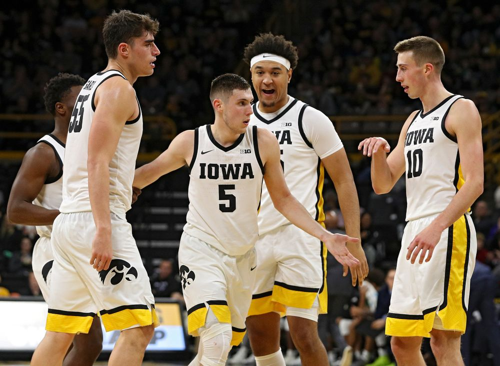 Iowa Hawkeyes guard CJ Fredrick (5) is greeted by guard Joe Toussaint (1), center Luka Garza (55), forward Cordell Pemsl (35), and guard Joe Wieskamp (10) after making a 3-pointer while being fouled during the second half of their game at Carver-Hawkeye Arena in Iowa City on Sunday, Nov 24, 2019. (Stephen Mally/hawkeyesports.com)