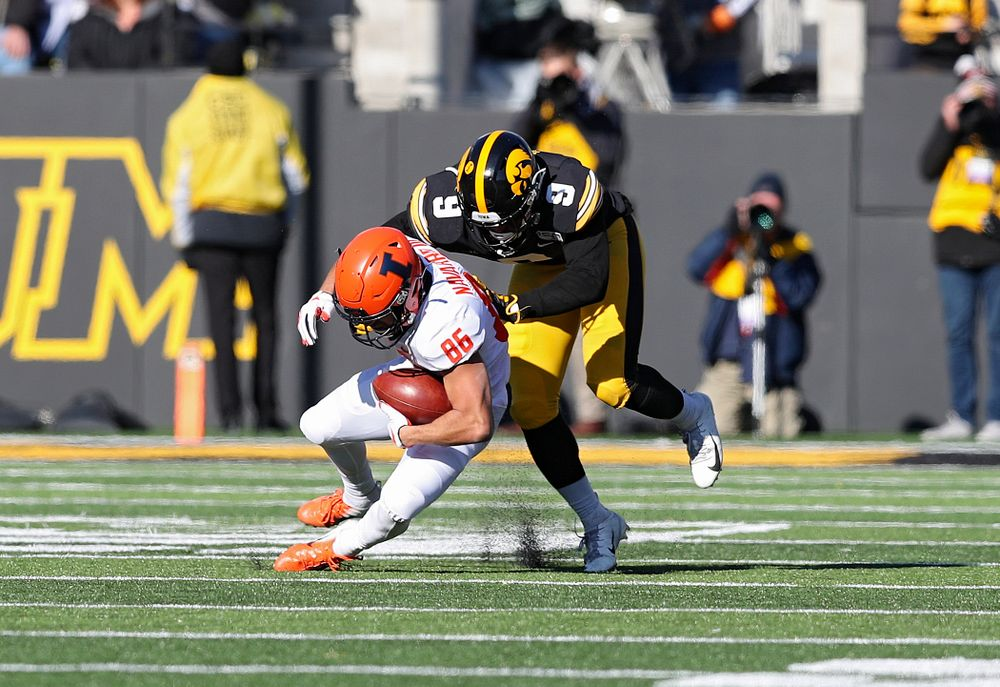 Iowa Hawkeyes defensive back Geno Stone (9) brings down Illinois Fighting Illini wide receiver Donny Navarro (86) during the third quarter of their game at Kinnick Stadium in Iowa City on Saturday, Nov 23, 2019. (Stephen Mally/hawkeyesports.com)