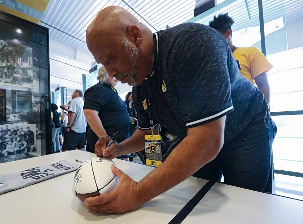 2019 University of Iowa Athletics Hall of Fame inductee Leroy Smith signs a football at the University of Iowa Athletics Hall of Fame in Iowa City on Friday, Aug 30, 2019. (Stephen Mally/hawkeyesports.com)