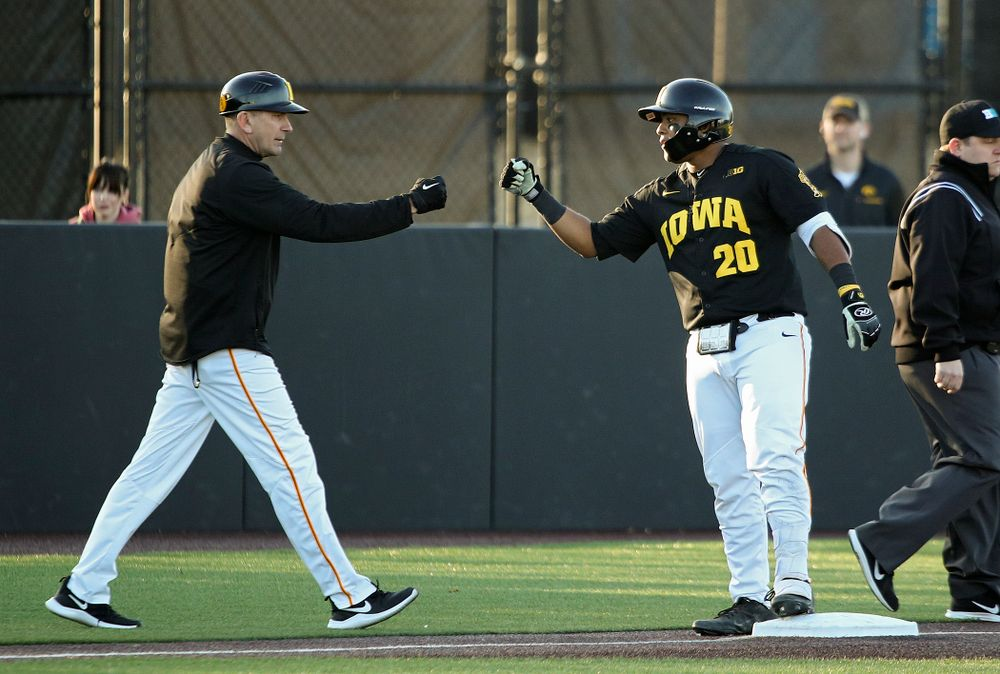 Iowa Hawkeyes head coach Rick Heller (from left) gives infielder Izaya Fullard (20) a first bump after he hit a triple during the third inning of their game at Duane Banks Field in Iowa City on Tuesday, March 3, 2020. (Stephen Mally/hawkeyesports.com)