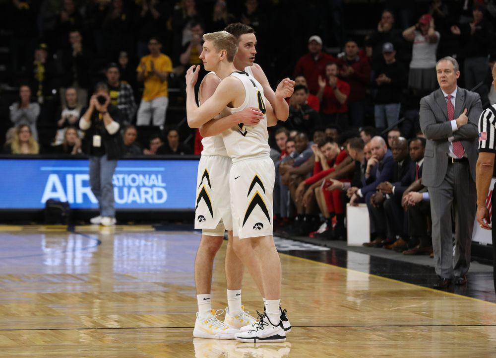 Iowa Hawkeyes forward Nicholas Baer (51) hugs his brother forward Michael Baer (0) as he leaves the court for the final time against the Rutgers Scarlet Knights Saturday, March 2, 2019 at Carver-Hawkeye Arena. (Brian Ray/hawkeyesports.com)