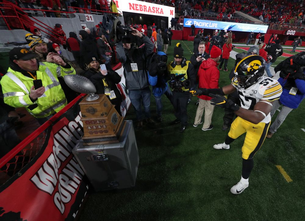 Iowa Hawkeyes defensive end Chauncey Golston (57) carries the Heroes Game trophy off the field following their win against the Nebraska Cornhuskers Friday, November 29, 2019 at Memorial Stadium in Lincoln, Neb. (Brian Ray/hawkeyesports.com)