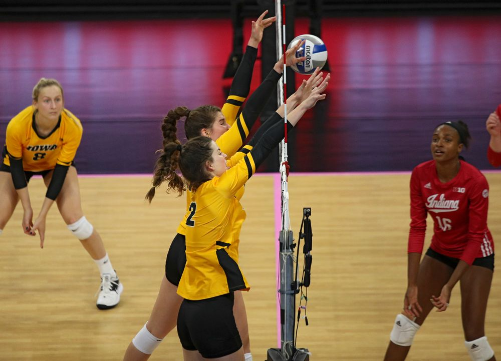 Iowa's Blythe Rients (11) gets her hands on a shot as Courtney Buzzerio (2) looks on during their match at Carver-Hawkeye Arena in Iowa City on Sunday, Oct 20, 2019. (Stephen Mally/hawkeyesports.com)