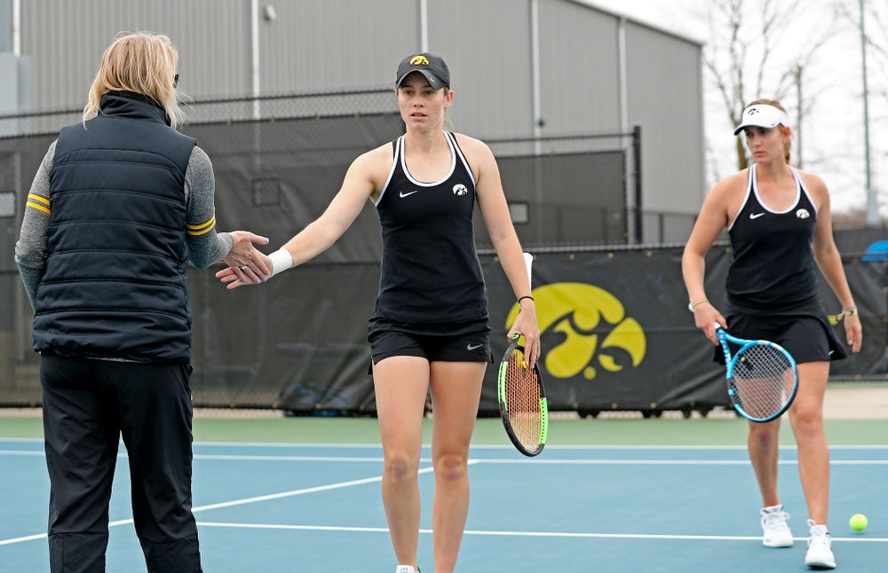 Iowa's head coach Sasha Schmid (from left) greets Elise van Heuvelen Treadwell and Ashleigh Jacobs during their doubles match against Rutgers at the Hawkeye Tennis and Recreation Complex in Iowa City on Friday, Apr. 5, 2019. (Stephen Mally/hawkeyesports.com)