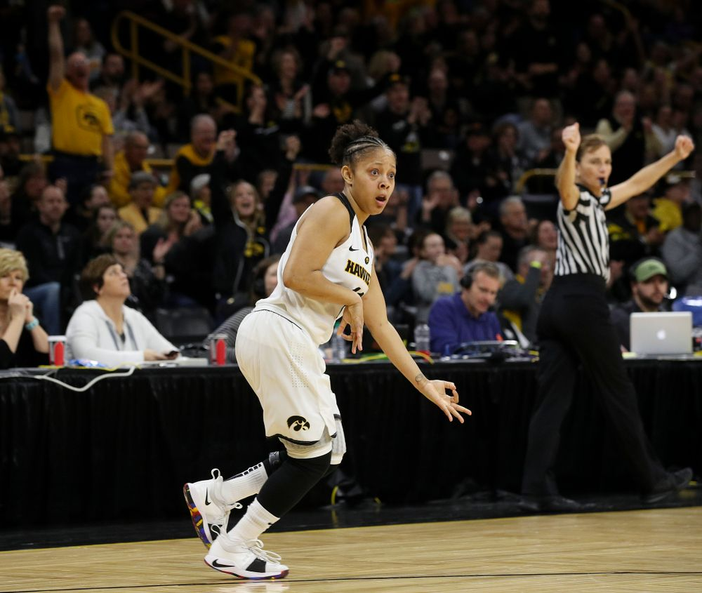 """Iowa Hawkeyes guard Tania Davis (11) plays the """"air guitar"""" as she celebrates after making a 3-pointer during the fourth quarter of their second round game in the 2019 NCAA Women's Basketball Tournament at Carver Hawkeye Arena in Iowa City on Sunday, Mar. 24, 2019. (Stephen Mally for hawkeyesports.com)"""