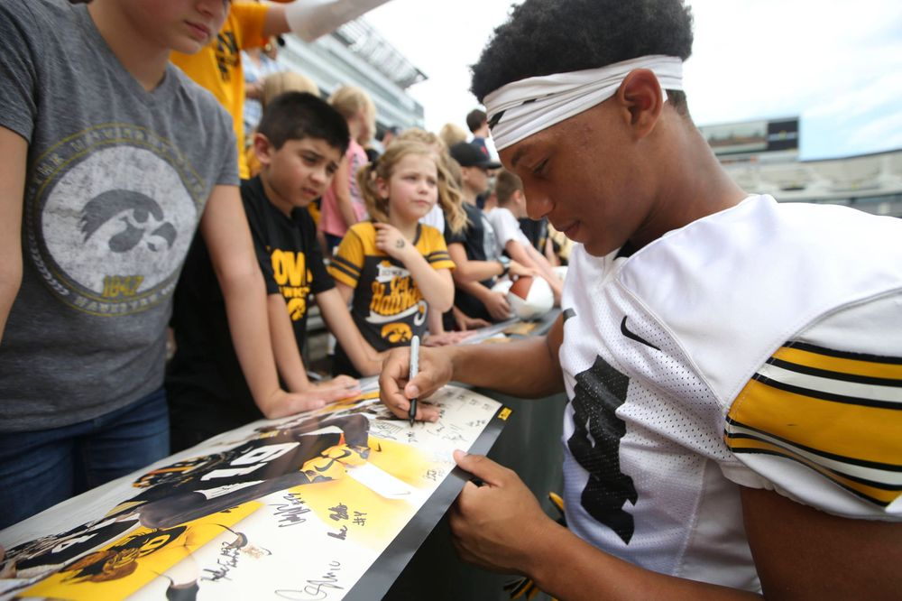 Iowa Hawkeyes defensive back Daraun McKinney (14) signs autographs during Kids Day at Kinnick Stadium on Saturday, August 10, 2019. (Lily Smith/hawkeyesports.com)