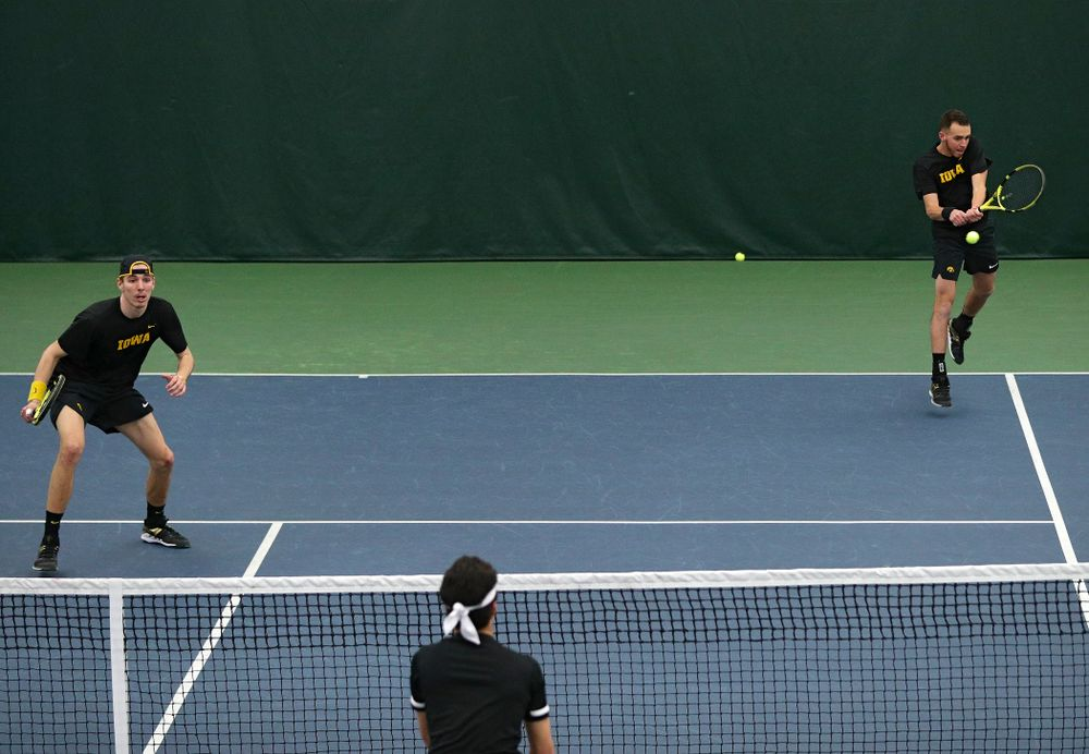 Iowa's Kareem Allaf (right) returns a shot as Nikita Snezhko (left) look son during their doubles match at the Hawkeye Tennis and Recreation Complex in Iowa City on Friday, March 6, 2020. (Stephen Mally/hawkeyesports.com)