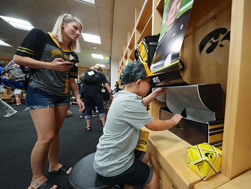 Kid Captain Jeg Weets looks at his gifts in his locker in the Iowa locker room during Kids Day at Kinnick Stadium in Iowa City on Saturday, Aug 10, 2019. (Stephen Mally/hawkeyesports.com)
