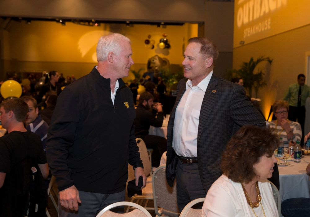 Offensive Line Coach Reese Morgan talks with LSU Tigers Head Coach Les Miles during a team dinner hosted by Outback Steakhouse Thursday, Dec. 26, 2013 in Tampa. (Brian Ray/hawkeyesports.com)