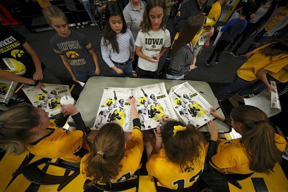 Iowa's Jaedynn Evans (22), Emma Grunkemeyer (14), Emily Bushman (12), and Grace Tubbs (16) sign autographs after their match at Carver-Hawkeye Arena in Iowa City on Sunday, Oct 20, 2019. (Stephen Mally/hawkeyesports.com)