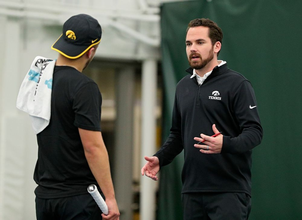 Iowa's Will Davies (from left) talks with head coach Ross Wilson during their match at the Hawkeye Tennis and Recreation Complex in Iowa City on Thursday, January 16, 2020. (Stephen Mally/hawkeyesports.com)