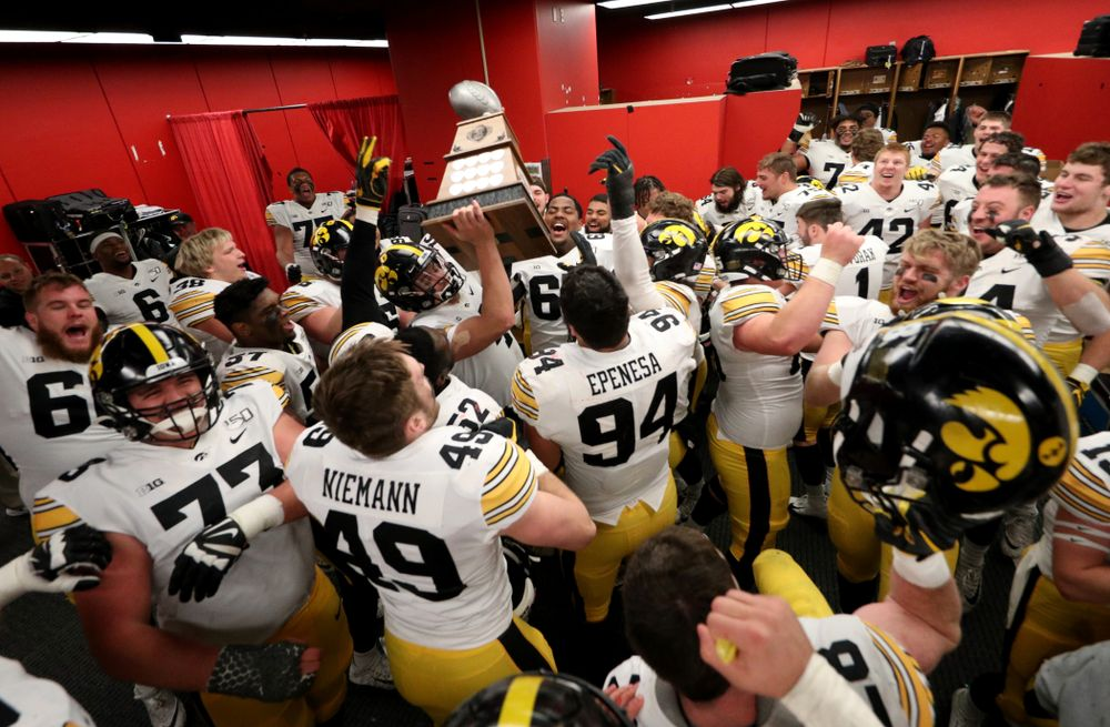 Iowa Hawkeyes quarterback Nate Stanley (4) hoists the Heroes Game trophy as they celebrate their win against the Nebraska Cornhuskers Friday, November 29, 2019 at Memorial Stadium in Lincoln, Neb. (Brian Ray/hawkeyesports.com)