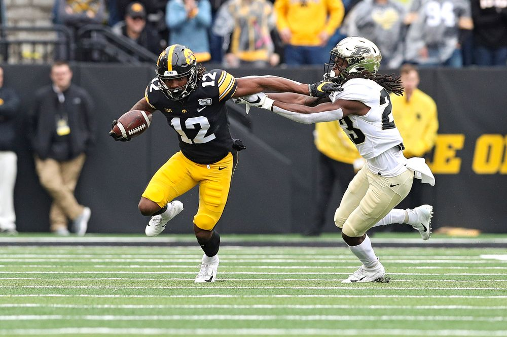 Iowa Hawkeyes wide receiver Brandon Smith (12) pulls away from a defender after making a catch during the first quarter of their game at Kinnick Stadium in Iowa City on Saturday, Oct 19, 2019. (Stephen Mally/hawkeyesports.com)