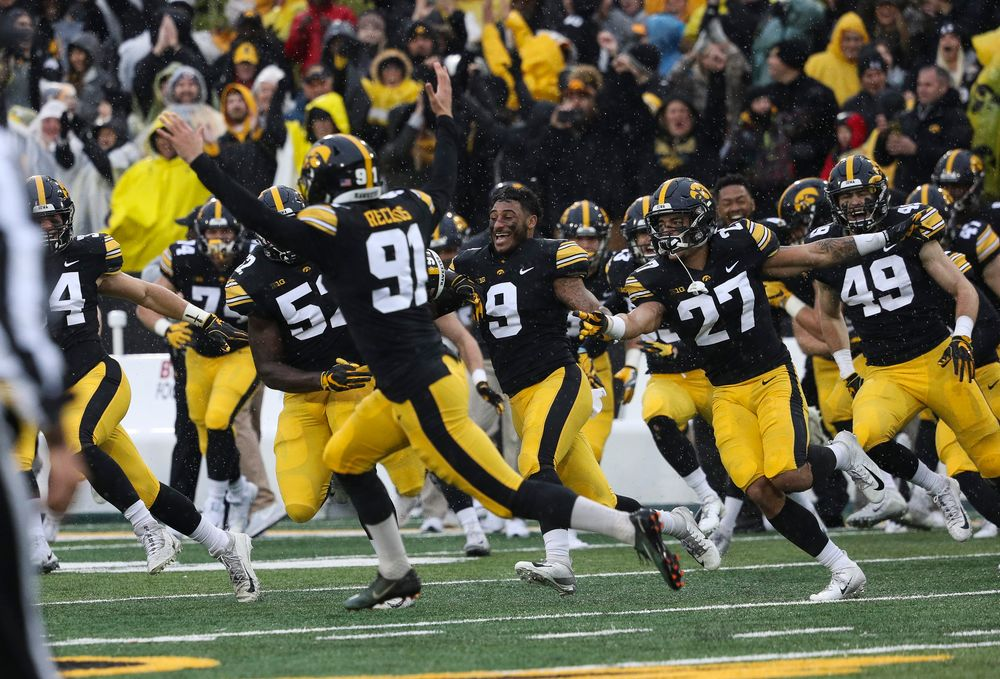 The Iowa Hawkeyes bench rushes the field after a game-winning 41-yard field goal by Iowa Hawkeyes placekicker Miguel Recinos (91) during a game against Nebraska at Kinnick Stadium on November 23, 2018. (Tork Mason/hawkeyesports.com)
