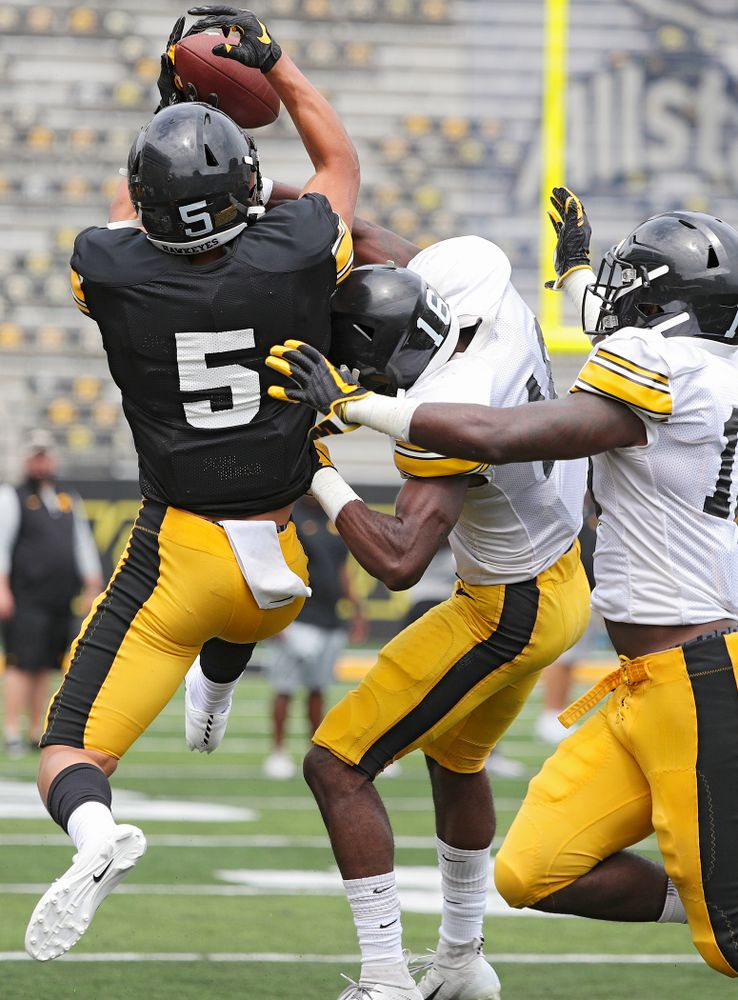 Iowa Hawkeyes wide receiver Oliver Martin (5) pulls in a pass as defensive back Terry Roberts (16) and defensive back Dallas Craddieth (15) defend during Fall Camp Practice No. 8 at Kids Day at Kinnick Stadium in Iowa City on Saturday, Aug 10, 2019. (Stephen Mally/hawkeyesports.com)