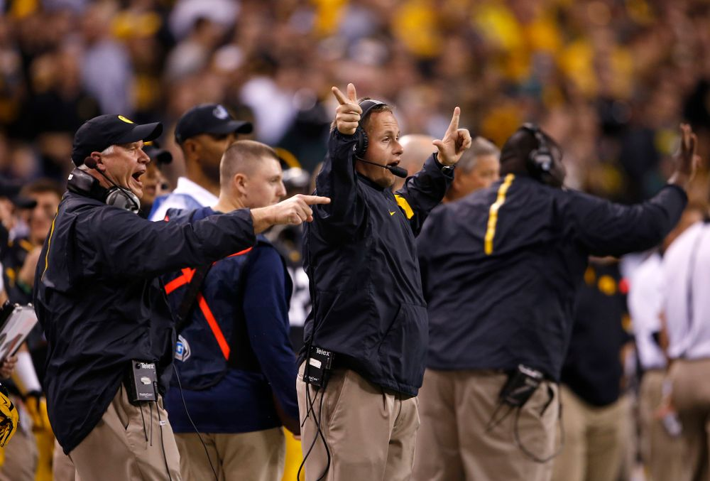 Iowa Hawkeyes defensive line coach Reese Morgan and defensive assistant Seth Wallace signal in a play during the first half against the Michigan State Spartans in the Big Ten Championship Game Saturday, December 5, 2015 at Lucas Oil Stadium in Indianapolis. (Brian Ray/hawkeyesports.com)