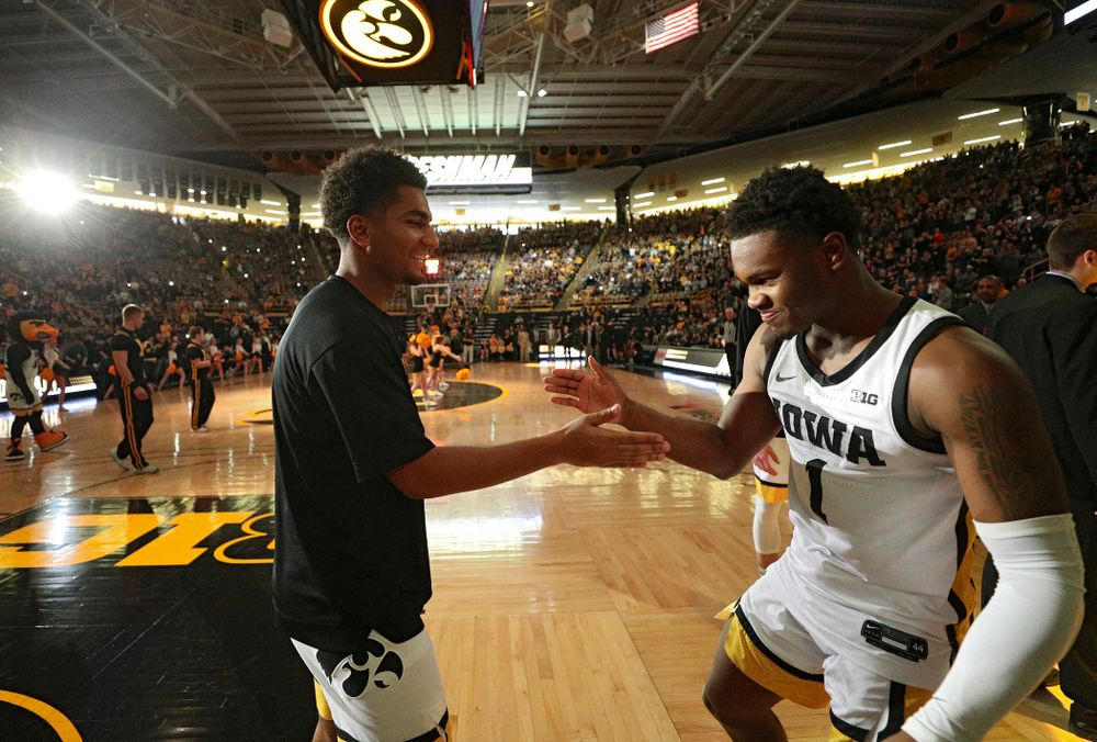 Iowa Hawkeyes guard Nicolas Hobbs (24) greets guard Joe Toussaint (1) as he is introduced before the game at Carver-Hawkeye Arena in Iowa City on Sunday, December 29, 2019. (Stephen Mally/hawkeyesports.com)