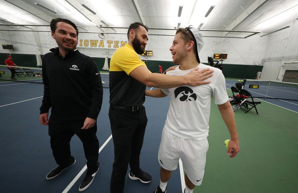 Iowa's Will Davies celebrates with his teammates after defeating Cornell's Lev Kazakov in three sets to clench at 4-3 victory Sunday, March 8, 2020 at the Hawkeye Tennis and Recreation Center. (Brian Ray/hawkeyesports.com)