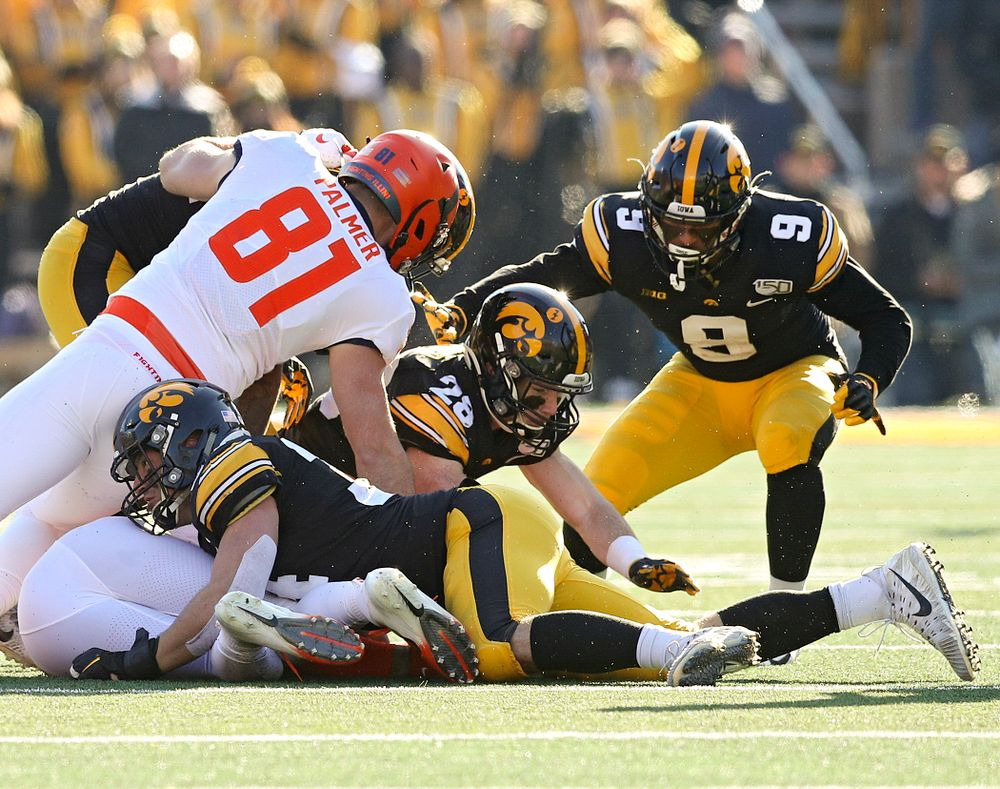 Iowa Hawkeyes defensive back Jack Koerner (28) recovers a fumble by Illinois Fighting Illini quarterback Brandon Peters (18) after it was forced out by linebacker Kristian Welch (34) as defensive back Geno Stone (9) closes in during the fourth quarter of their game at Kinnick Stadium in Iowa City on Saturday, Nov 23, 2019. (Stephen Mally/hawkeyesports.com)