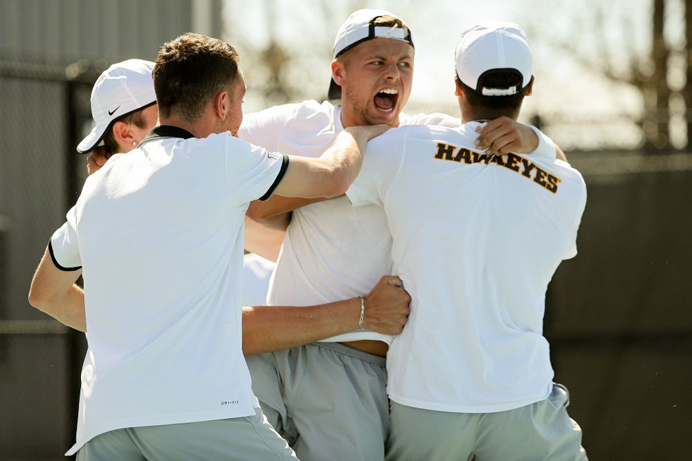 Iowa's Will Davies celebrates with teammates after winning his match against Michigan at the Hawkeye Tennis and Recreation Complex in Iowa City on Sunday, Apr. 21, 2019. (Stephen Mally/hawkeyesports.com)