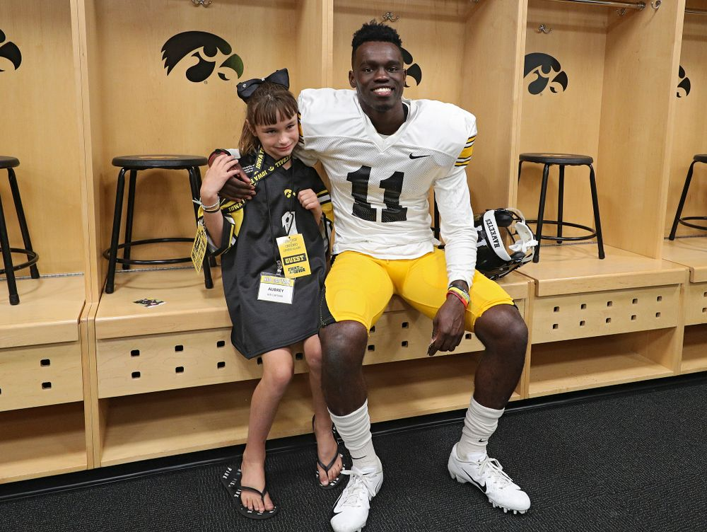 Kid Captain Aubrey Bussan-Kluesner takes a picture with defensive back Michael Ojemudia (11) during Kids Day at Kinnick Stadium in Iowa City on Saturday, Aug 10, 2019. (Stephen Mally/hawkeyesports.com)