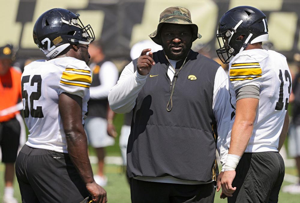Iowa Hawkeyes defensive line coach Kelvin Bell talks with linebacker Amani Jones (52) and linebacker Joe Evans (13) during Fall Camp Practice No. 7 at the Hansen Football Performance Center in Iowa City on Friday, Aug 9, 2019. (Stephen Mally/hawkeyesports.com)