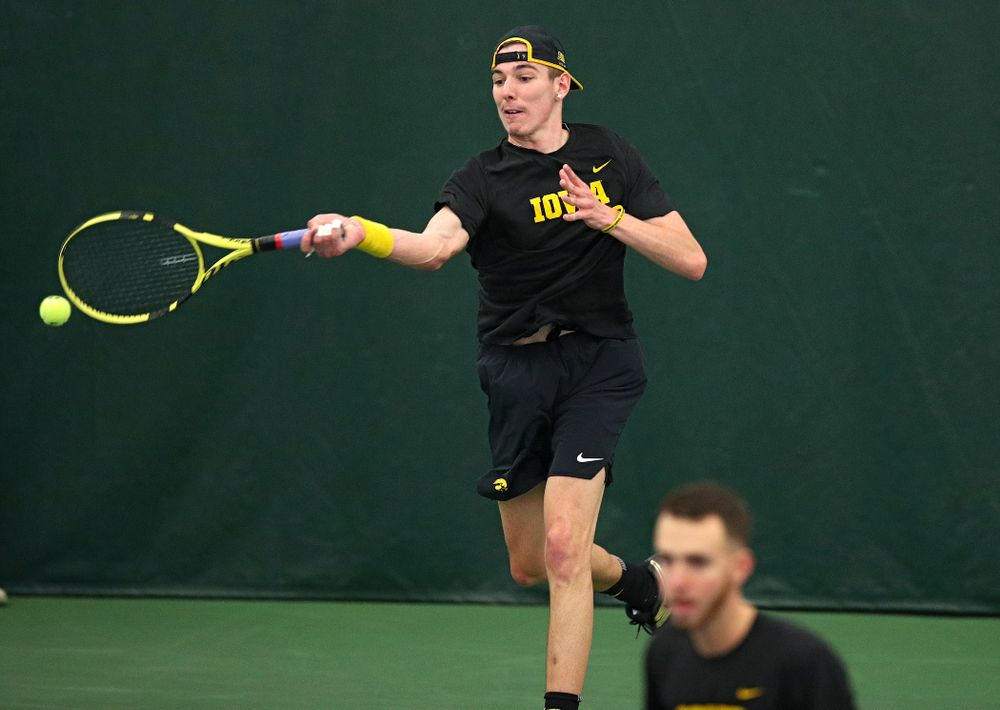 Iowa's Nikita Snezhko (top) returns a shot as Kareem Allaf looks on during their doubles match at the Hawkeye Tennis and Recreation Complex in Iowa City on Friday, March 6, 2020. (Stephen Mally/hawkeyesports.com)