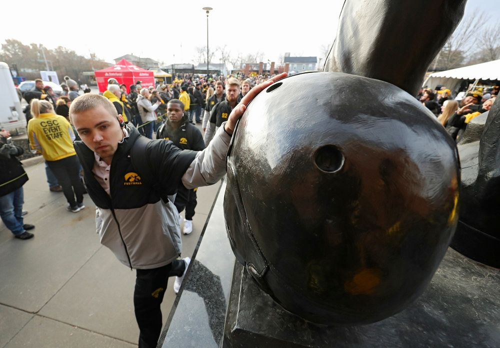 Iowa Hawkeyes quarterback Nate Stanley (4) touches the helmet on the Nile Kinnick statue before their game at Kinnick Stadium in Iowa City on Saturday, Nov 23, 2019. (Stephen Mally/hawkeyesports.com)