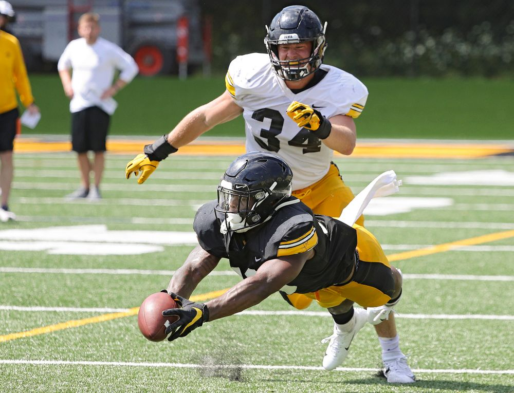 Iowa Hawkeyes running back Mekhi Sargent (10) dives for a pass as linebacker Kristian Welch (34) looks on during Fall Camp Practice #5 at the Hansen Football Performance Center in Iowa City on Tuesday, Aug 6, 2019. (Stephen Mally/hawkeyesports.com)