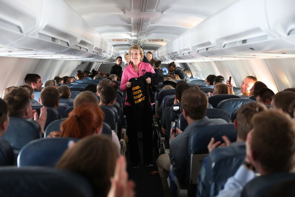 Iowa Hawkeyes head coach Lisa Bluder hands out t-shirts to the band and spirit squad on board the team plane to Greensboro, NC for the Regionals of the 2019 NCAA Women's Basketball Championships Thursday, March 28, 2019 at the Eastern Iowa Airport. (Brian Ray/hawkeyesports.com)