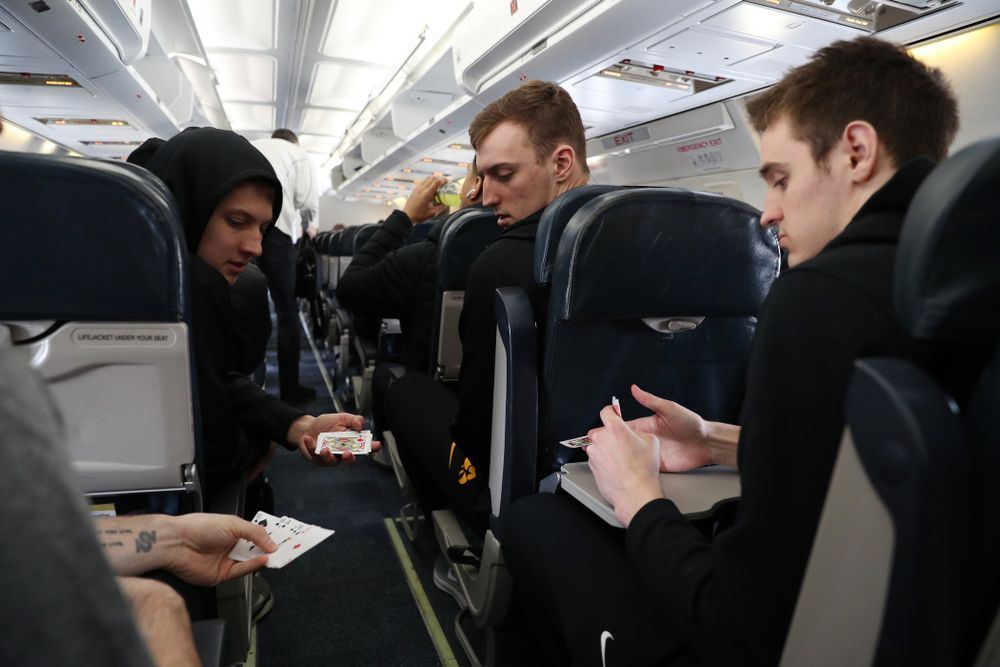 Iowa Hawkeyes guard Connor McCaffery (30), guard Austin Ash (13), forward Jack Nunge (2) forward Nicholas Baer (51) play cards on a flight to Columbus for the first and second rounds of the 2019 NCAA Men's Basketball Tournament Wednesday, March 20, 2019 at the Eastern Iowa Airport. (Brian Ray/hawkeyesports.com)