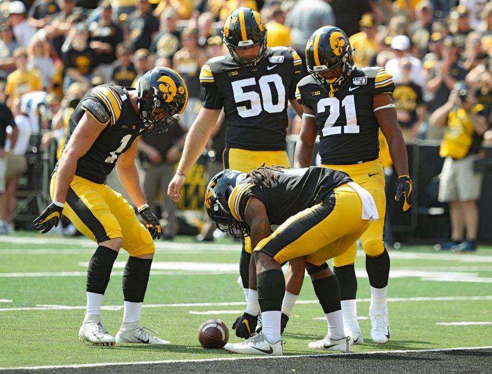 Iowa Hawkeyes defensive back Wes Dvorak (1), long snapper Jackson Subbert (50), and running back Ivory Kelly-Martin (21) gather around as defensive back Devonte Young (17) downs a punt at the 1-yard line during the fourth quarter of their Big Ten Conference football game at Kinnick Stadium in Iowa City on Saturday, Sep 7, 2019. (Stephen Mally/hawkeyesports.com)