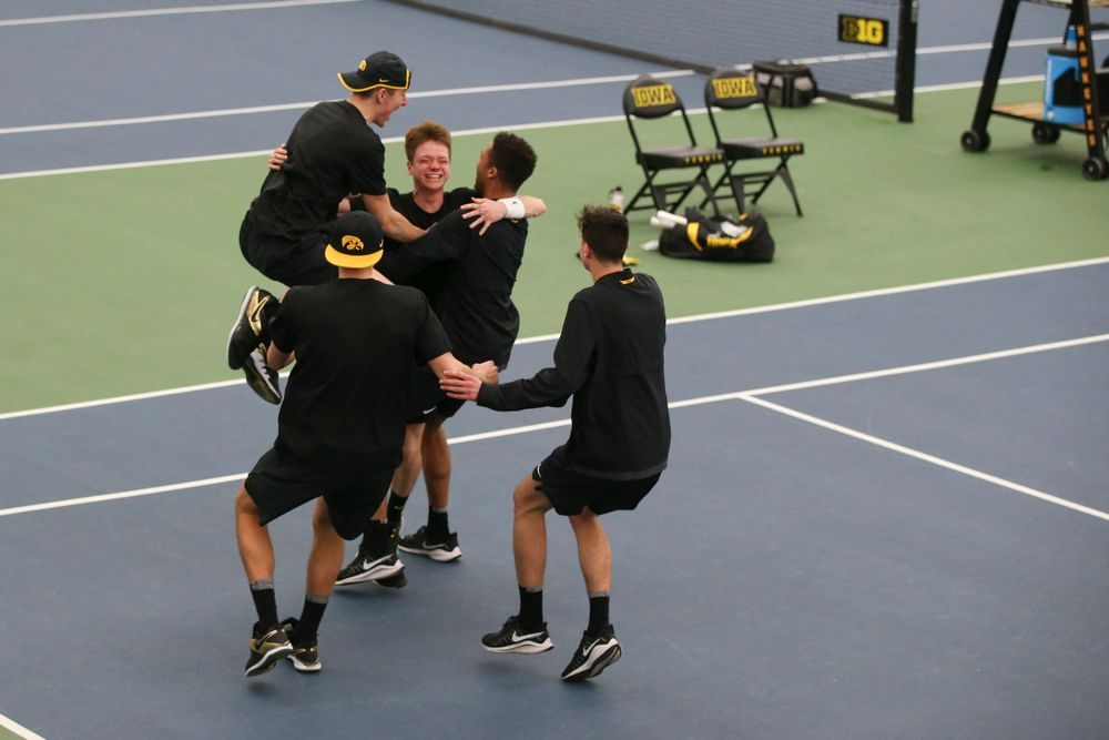 The Iowa men's tennis team celebrates with Jason Kerst in his singles win to clinch the win over VCU on Saturday, February 29, 2020 at the Hawkeye Tennis and Recreation Complex. (Lily Smith/hawkeyesports.com)