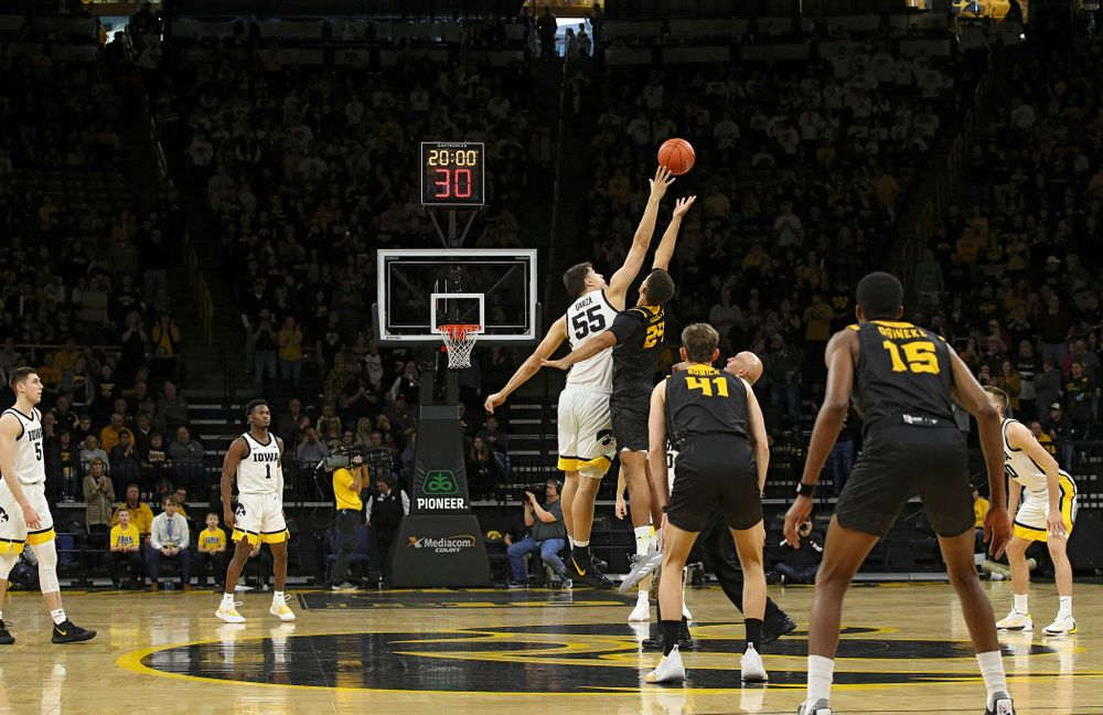 Iowa Hawkeyes center Luka Garza (55) wins the opening tipoff during the first half of their their game at Carver-Hawkeye Arena in Iowa City on Sunday, December 29, 2019. (Stephen Mally/hawkeyesports.com)