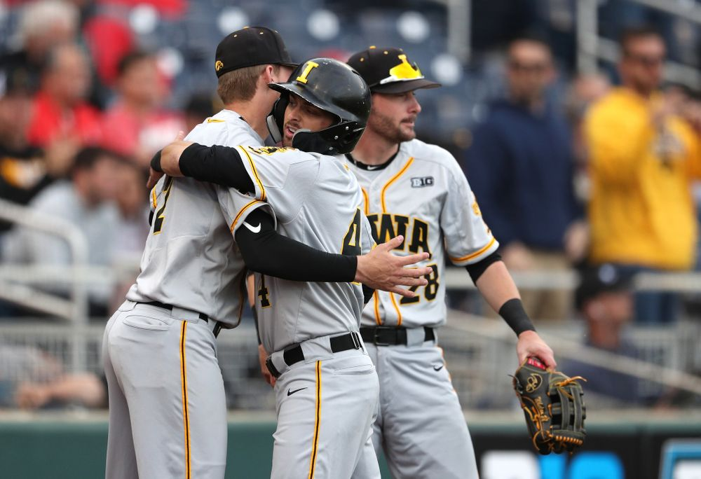 Iowa Hawkeyes infielder Mitchell Boe (4) hugs infielder Brendan Sher (2) after scoring against the Indiana Hoosiers in the first round of the Big Ten Baseball Tournament Wednesday, May 22, 2019 at TD Ameritrade Park in Omaha, Neb. (Brian Ray/hawkeyesports.com)