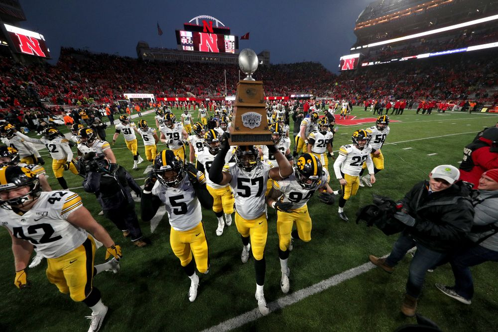 The Iowa Hawkeyes celebrate with the Heroes Game trophy following their win against the Nebraska Cornhuskers Friday, November 29, 2019 at Memorial Stadium in Lincoln, Neb. (Brian Ray/hawkeyesports.com)