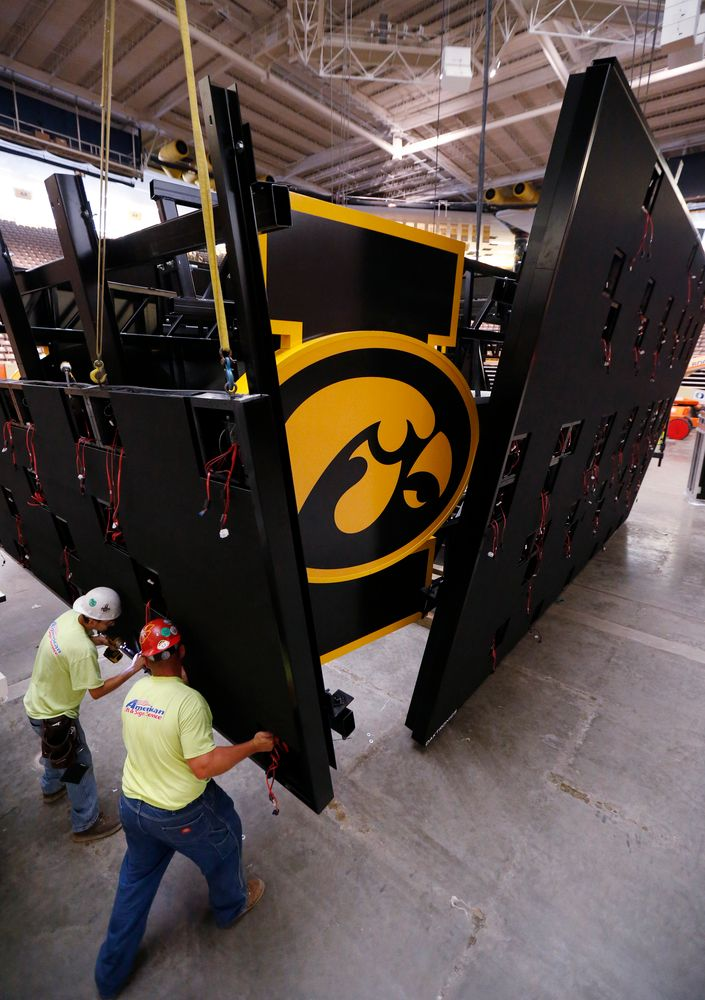 Workers install the panels on the new centerhung video board