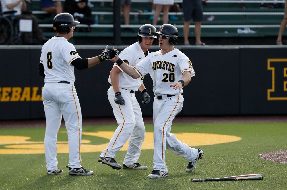 Iowa Hawkeyes catcher Austin Guzzo (20) celebrates with outfielder Luke Farley (8) after scoring against the Oklahoma State Cowboys Saturday, May 5, 2018 at Duane Banks Field. (Brian Ray/hawkeyesports.com)