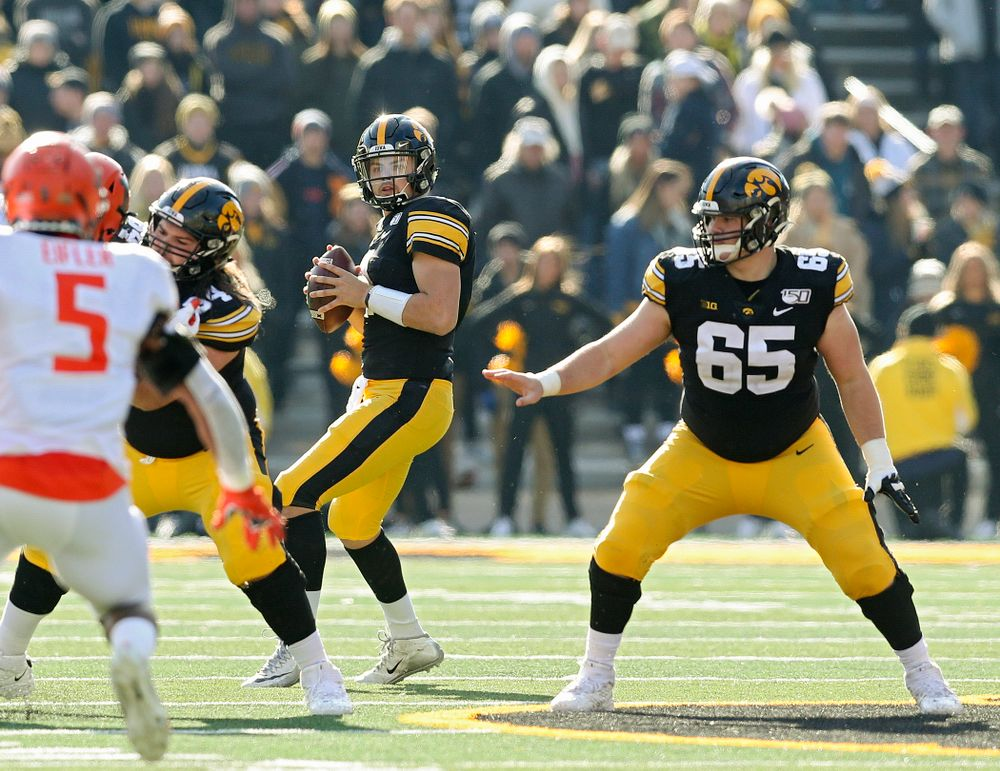 Iowa Hawkeyes quarterback Nate Stanley (4) looks to pass behind a block by offensive lineman Kyler Schott (64) as offensive lineman Tyler Linderbaum (65) looks to block during the second quarter of their game at Kinnick Stadium in Iowa City on Saturday, Nov 23, 2019. (Stephen Mally/hawkeyesports.com)