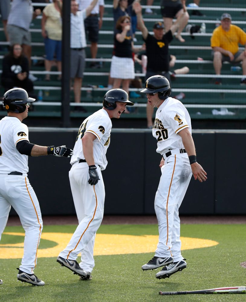 Iowa Hawkeyes catcher Austin Guzzo (20) celebrates with outfielder Robert Neustrom (44) after scoring against the Oklahoma State Cowboys Saturday, May 5, 2018 at Duane Banks Field. (Brian Ray/hawkeyesports.com)