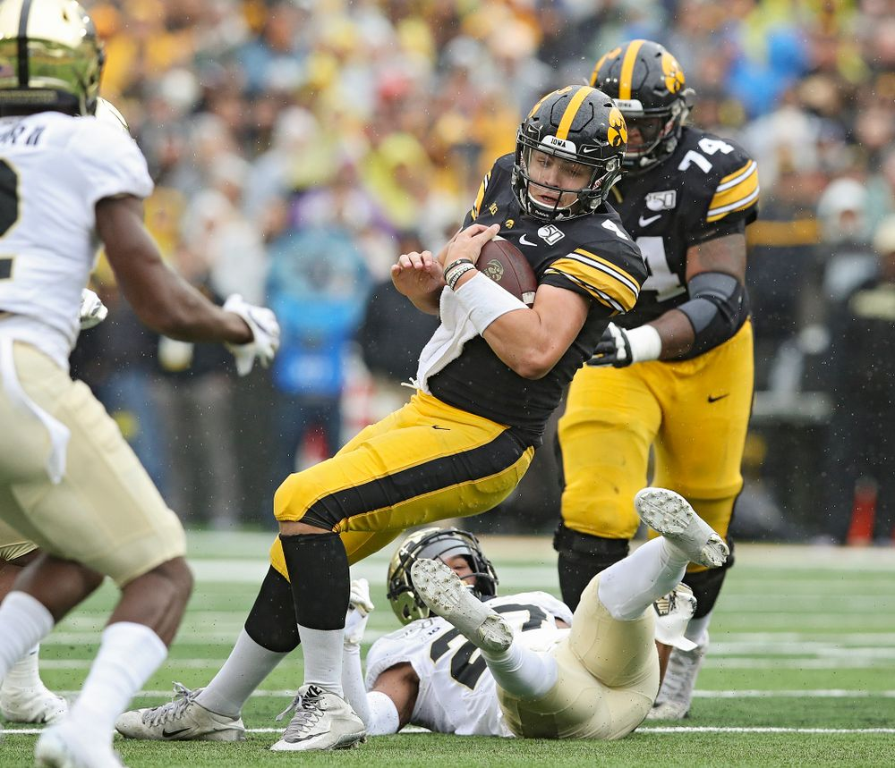 Iowa Hawkeyes quarterback Nate Stanley (4) spins away from a defender on a run during the third quarter of their game at Kinnick Stadium in Iowa City on Saturday, Oct 19, 2019. (Stephen Mally/hawkeyesports.com)