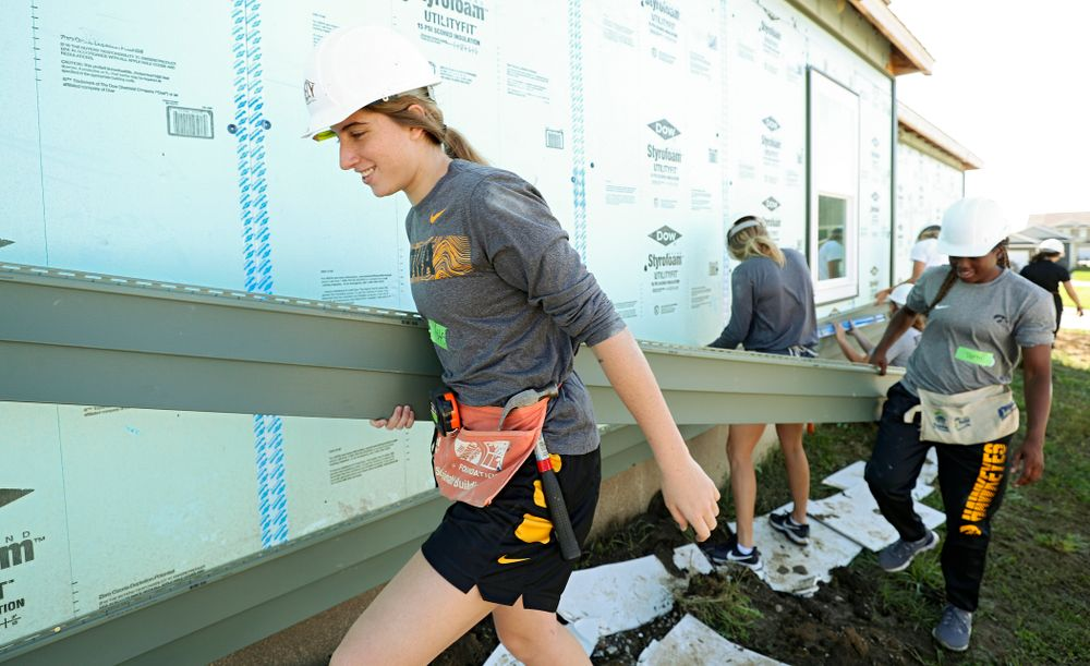 Iowa's Kate Martin (from left) and Tomi Taiwo carry a piece of siding as they work on a Habitat for Humanity Women Build project in Iowa City on Wednesday, Sep 25, 2019. (Stephen Mally/hawkeyesports.com)