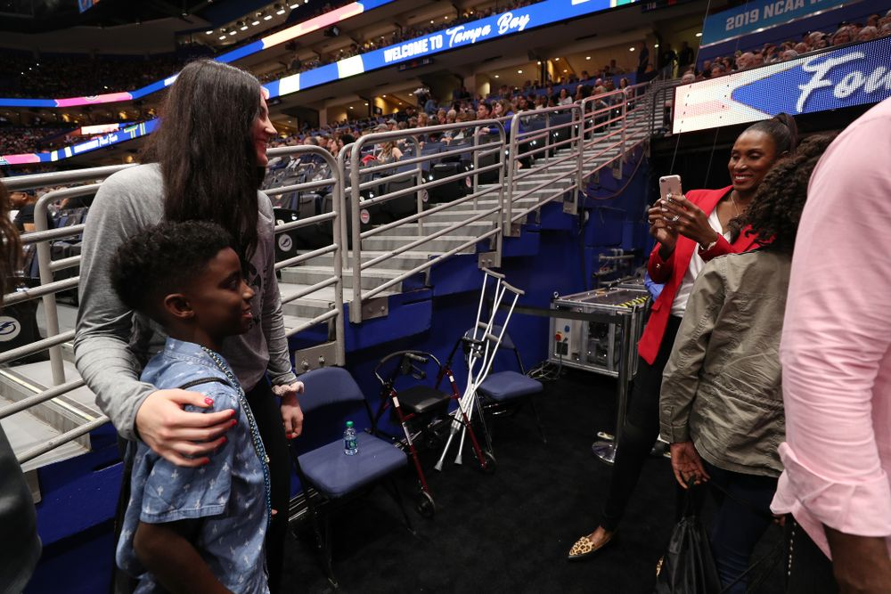 Iowa Hawkeyes forward Megan Gustafson (10) talks with Lisa Leslie and her family before being introduced during a timeout in the second half of the National Semi-Final between Baylor and Oregon Friday, April 5, 2019 at Amalie Arena in Tampa, FL. (Brian Ray/hawkeyesports.com)