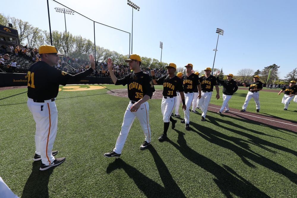 Iowa Hawkeyes head coach Rick Heller high fives starting pitcher Cam Baumann (35) following game two against UC Irvine Saturday, May 4, 2019 at Duane Banks Field. (Brian Ray/hawkeyesports.com)