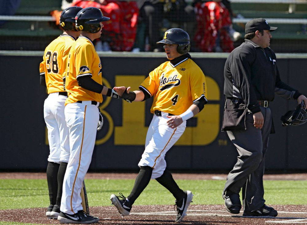 Iowa Hawkeyes infielder Mitchell Boe (right) slaps hands with Zeb Adreon (left) after they both scored during the third inning against Illinois at Duane Banks Field in Iowa City on Sunday, Mar. 31, 2019. (Stephen Mally/hawkeyesports.com)