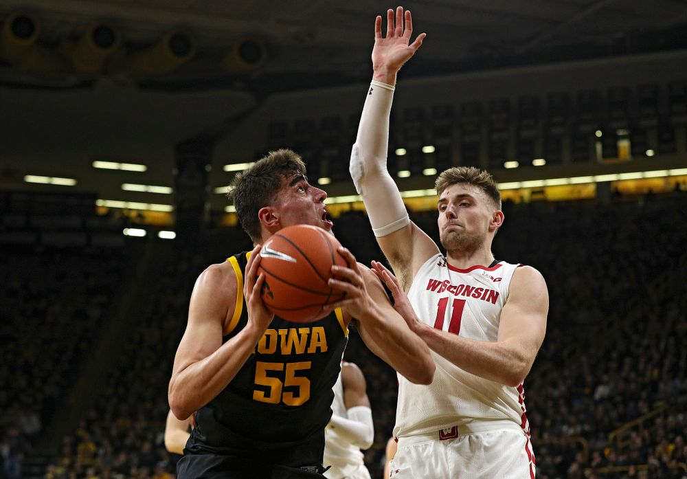 Iowa Hawkeyes center Luka Garza (55) eyes the basket before scoring around Wisconsin Badgers forward Micah Potter (11) during the first half of their game at Carver-Hawkeye Arena in Iowa City on Monday, January 27, 2020. (Stephen Mally/hawkeyesports.com)